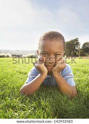 Portrait of boy laying in grass with head resting on hands - stock photo