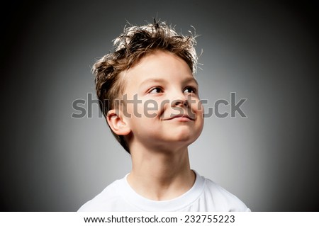 Portrait of boy looks into the distance on gray background - stock photo