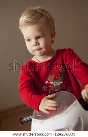 Portrait of Boy on a toy motorcycle - stock photo