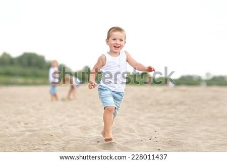 Portrait of boy on the beach in summer - stock photo