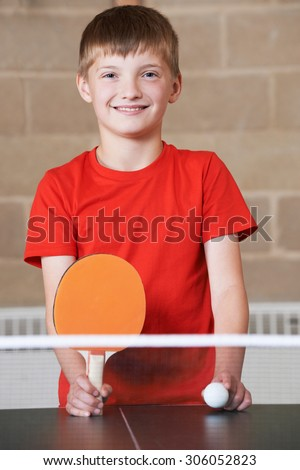 Portrait Of Boy Playing Table Tennis In School Gym - stock photo