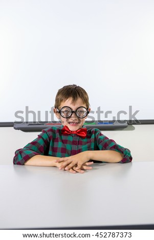 Portrait of boy sitting at table against whiteboard in classroom - stock photo
