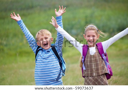 portrait of  boy with girl joyful laugh and throw their hands up - stock photo