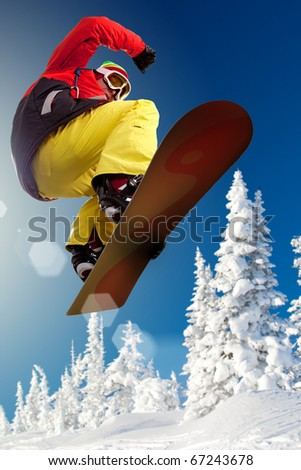 Portrait of boy with snowboard jumping near snowy forest - stock photo