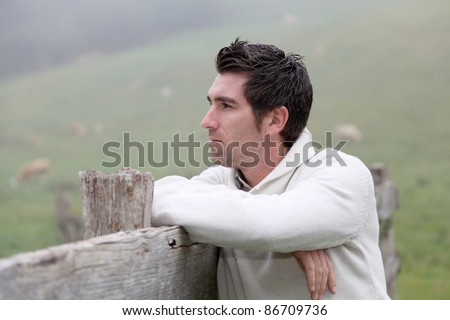 Portrait of breeder leaning on fence - stock photo