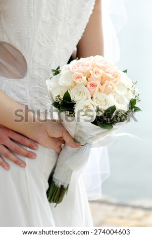 portrait of bride holding a bouquet behind her back - stock photo