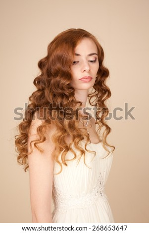 Portrait of bride with curly hairstyle and beautiful makeup looking down - stock photo