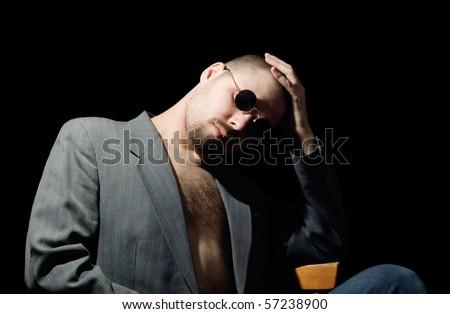 portrait of bristly man in coat in the dark - stock photo