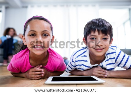 Portrait of brother and sister lying on floor with digital tablet in living room - stock photo