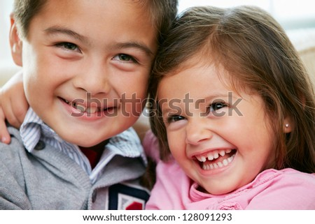 Portrait Of Brother And Sister Sitting On Sofa Together - stock photo