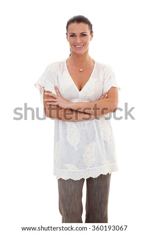Portrait of brunette, casual businesswoman standing with arms crossed, looking at camera, white background. - stock photo