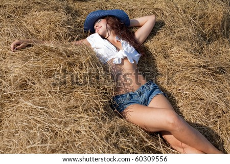 Portrait of brunette girl in shorts and hat. Young woman in costume of cowboy lies on haystack - stock photo