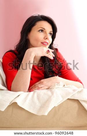 Portrait of brunette girl sitting on the sofa - stock photo