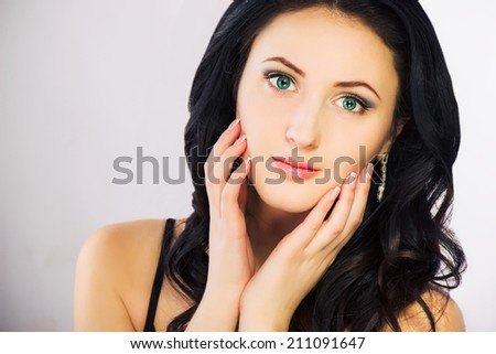 Portrait of brunette girl with green eyes on grey background - stock photo