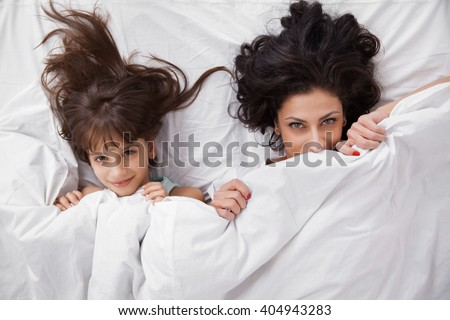 Portrait of brunette long hair mother and daughter under the duvet together in soft morning light on white linen bed. Concept of happy family living, relaxation, comfort, fun. Top view. - stock photo