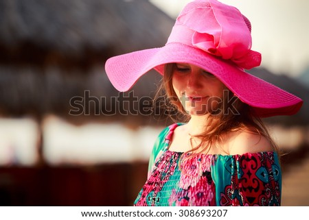portrait of brunette longhaired girl in big red hat looking down against defocused reed umbrella - stock photo