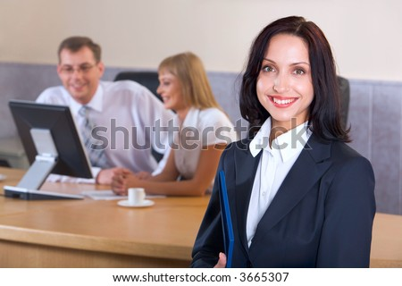 Portrait of brunette smiling businesswoman staring at camera holding blue paper case in her hands and two businesspeople on the background looking at the monitor - stock photo