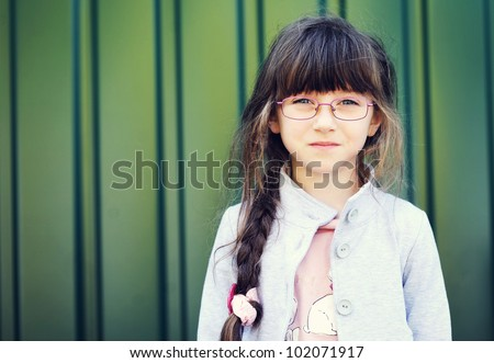 Portrait of brunette toddler girl in glasses against green wall - stock photo