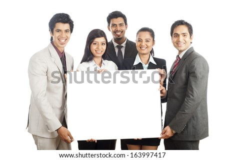 Portrait of business executives holding a placard and smiling - stock photo
