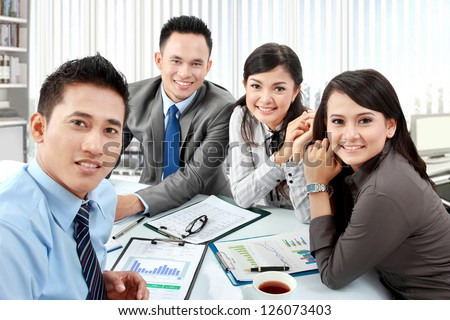 Portrait of business group meeting around a table with many paperwork - stock photo