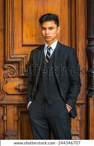 Portrait of Business Man. Dressing formally in three pieces black suit, patterned necktie, vest, hands in pockets, a young businessman is standing by an old fashion style office door, looking at you. - stock photo