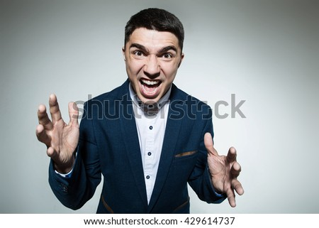 Portrait of business man screaming in anger and looking at camera. Human emotion expression and lifestyle concept. - stock photo
