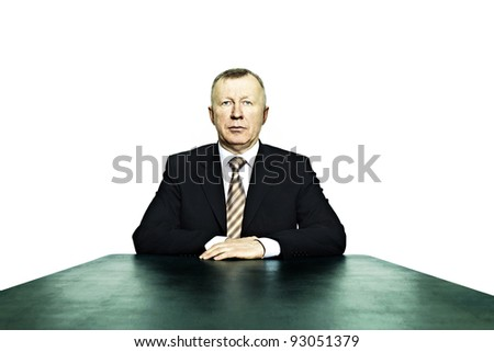 Portrait of business man sitting at the head of the table - stock photo