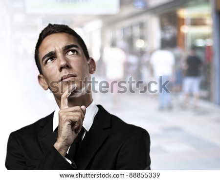portrait of business man thinking against a crowded place - stock photo