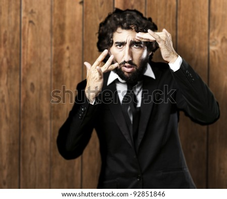 portrait of business man touching his face against a wooden wall - stock photo