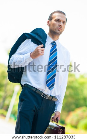 Portrait of business man walking with suit droped over shoulder in park - stock photo