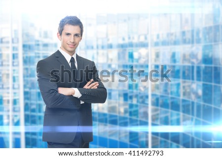 Portrait of business man with crossed hands, blue background. Concept of leadership and success - stock photo