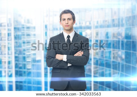 Portrait of business man with crossed hands, isolated on blue background. Concept of leadership and success - stock photo
