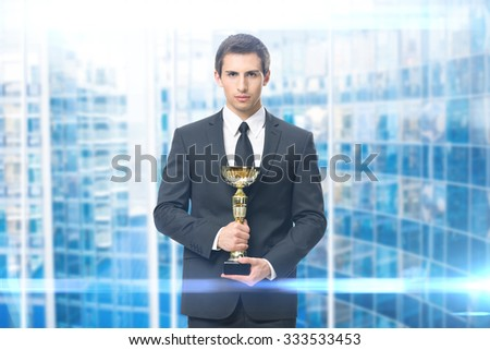 Portrait of business man with gold cup, blue background. Concept of leadership and success - stock photo