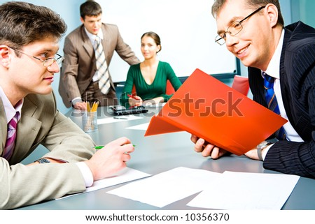 Portrait of business men sitting at the table and brainstorming on the background of people - stock photo