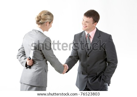 Portrait of business partners handshaking while female holding knife behind her back - stock photo