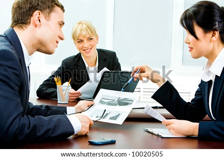 Portrait of business partners holding business documents and discussing them while their colleague looking at them with smile - stock photo