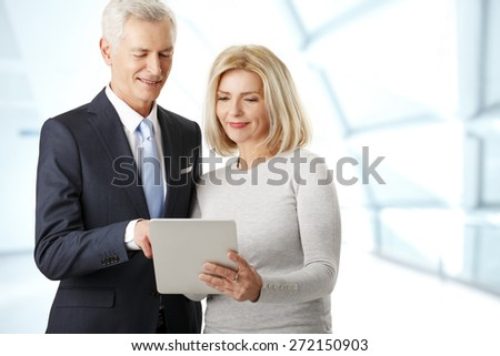 Portrait of business people consulting. Middle age businesswoman standing at office and holding digital tablet while consulting with senior businessman from the new project. Teamwork.  - stock photo