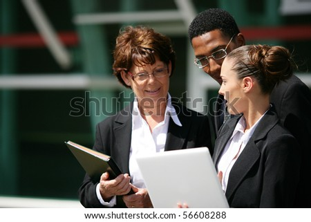 Portrait of business people in suit holding documents and a laptop computer - stock photo
