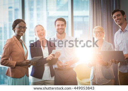 Portrait of business people interacting using mobile phone, digital tablet and laptop in the office - stock photo