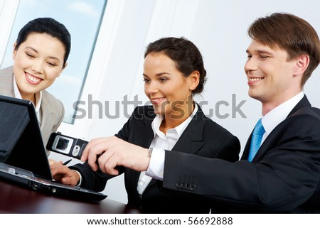 Portrait of business people looking at laptop where man showing - stock photo