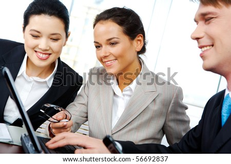 Portrait of business people looking at laptop while sharing their ideas about new project - stock photo