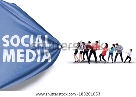 Portrait of business team pulling together a banner of social media - stock photo