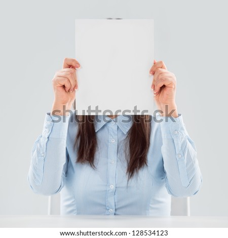 Portrait of business woman holding blank paper sheet in front of her face - stock photo