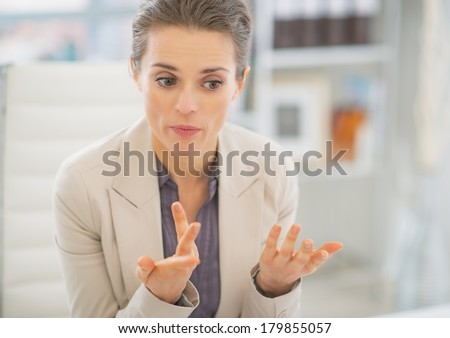 Portrait of business woman in office explaining something - stock photo