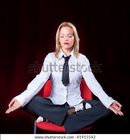 Portrait of business woman meditating on the chair in the office, red background - stock photo