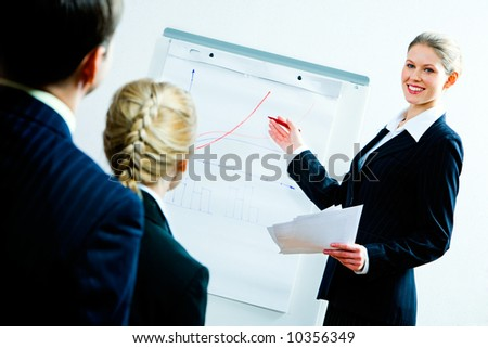 Portrait of business woman showing a plan of development to co-workers - stock photo