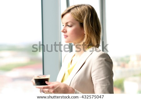 Portrait of business woman standing with coffee near window - stock photo