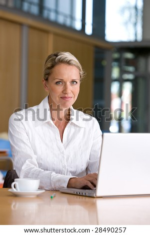Portrait of business woman working on laptop - stock photo