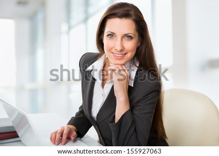 Portrait of business woman working with laptop - stock photo