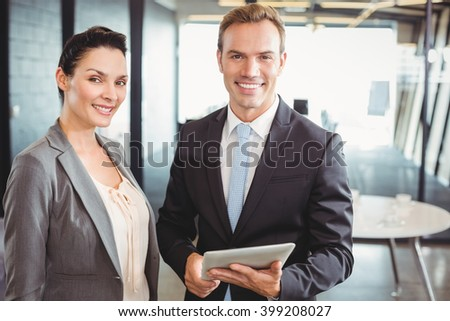 Portrait of businessman and businesswoman holding digital tablet at office - stock photo